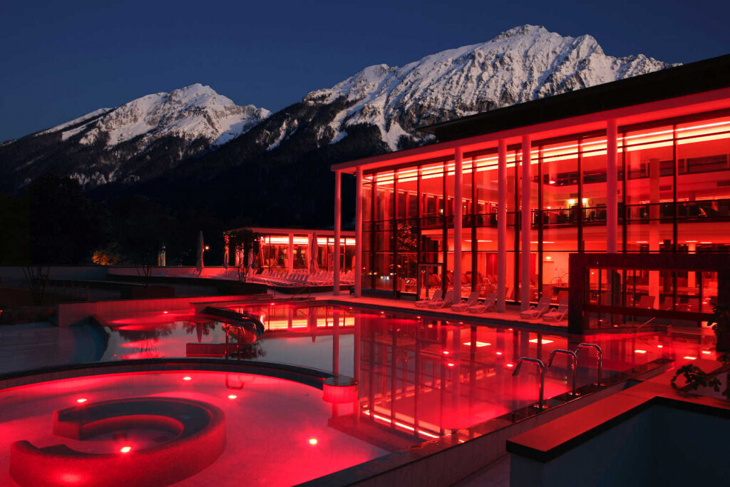 Rupertustherme Bad Reichenhall in roter Beleuchtung bei Nacht vor Bergpanorama